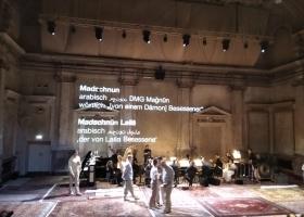 """Bühnenbild Oper """"Leyla und Medjnun"""", Menschen und projizierter Text auf einer Bühne"""